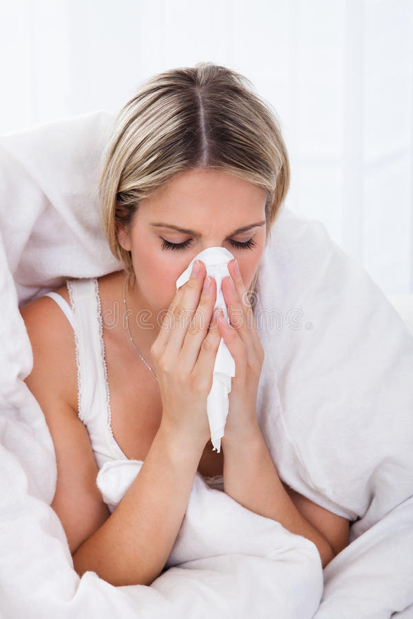 Sjuk kvinna som blåser henne näsa fotografering för bildbyråer