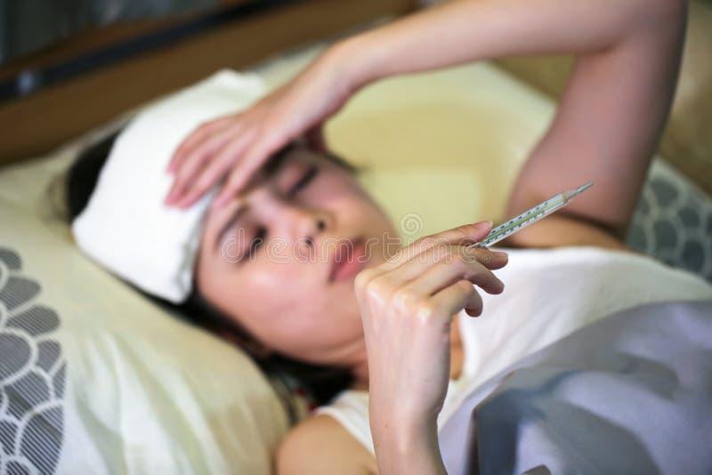 Sjuk kvinna som har en influensa med att mäta temperatur i säng royaltyfria foton