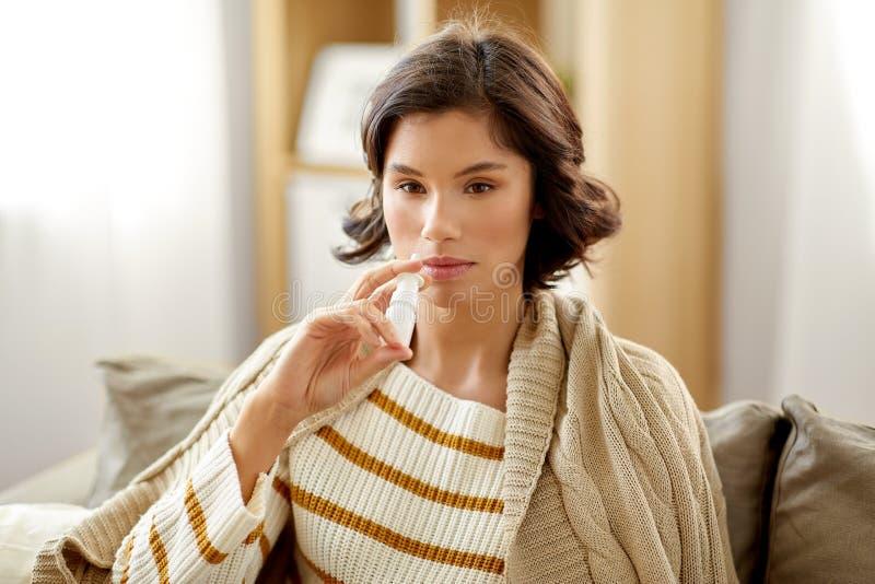 Sjuk kvinna som hemma använder nasal sprej fotografering för bildbyråer