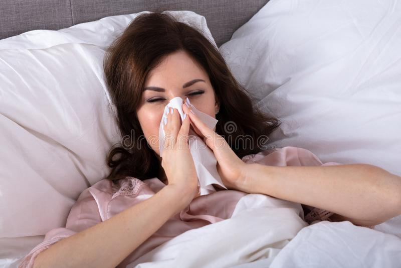 Sjuk kvinna som nyser i n?sduk royaltyfri fotografi