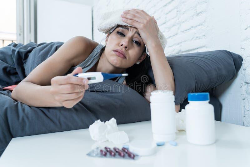 Sjuk latinsk kvinna i säng med en feber och en förkylning royaltyfri bild