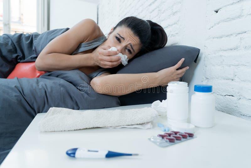 Sjuk latinsk kvinna i säng med en feber och en förkylning royaltyfria foton
