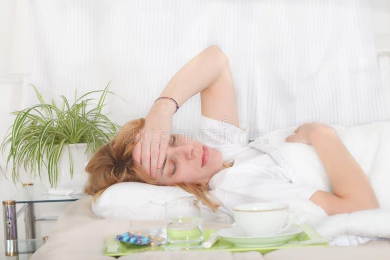 Sjuk layin för ung kvinna i sängen med influensa och feber arkivbilder