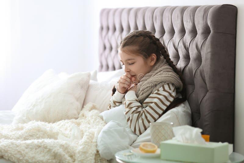 Sjuk liten flicka med hostalidande från förkylning arkivbilder