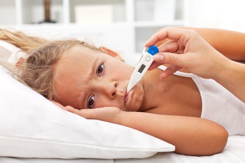 Sjuk liten flicka med termometern som lägger i säng royaltyfri fotografi