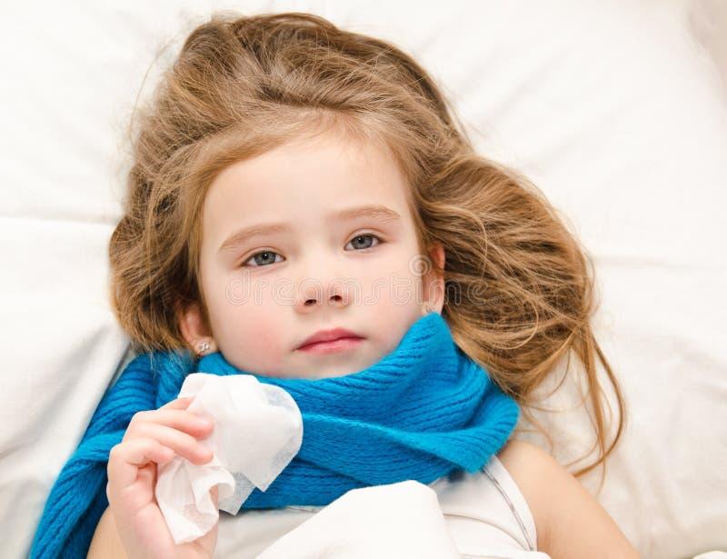 Sjuk liten flicka som ligger i sängen med halsduken och silkespappret arkivfoton