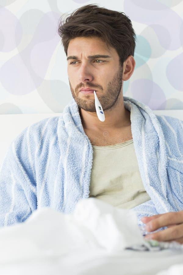 Sjuk man med termometern i munsammanträde på säng royaltyfri bild