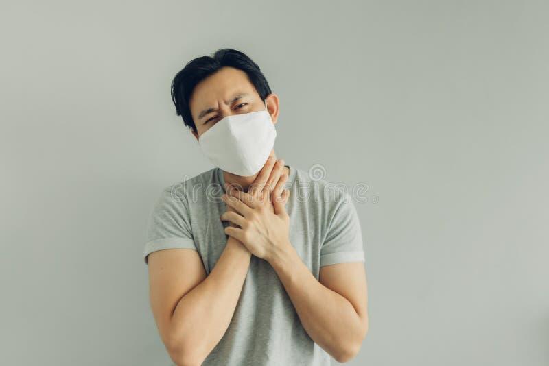 Sjuk man med vit hygienmask i grå t-tröja i begreppet virus royaltyfri foto
