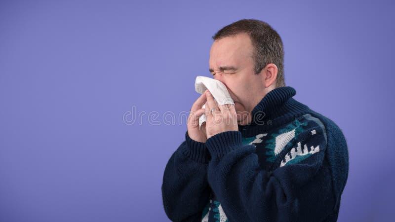 Sjuk man som blåser hans näsa arkivfoto