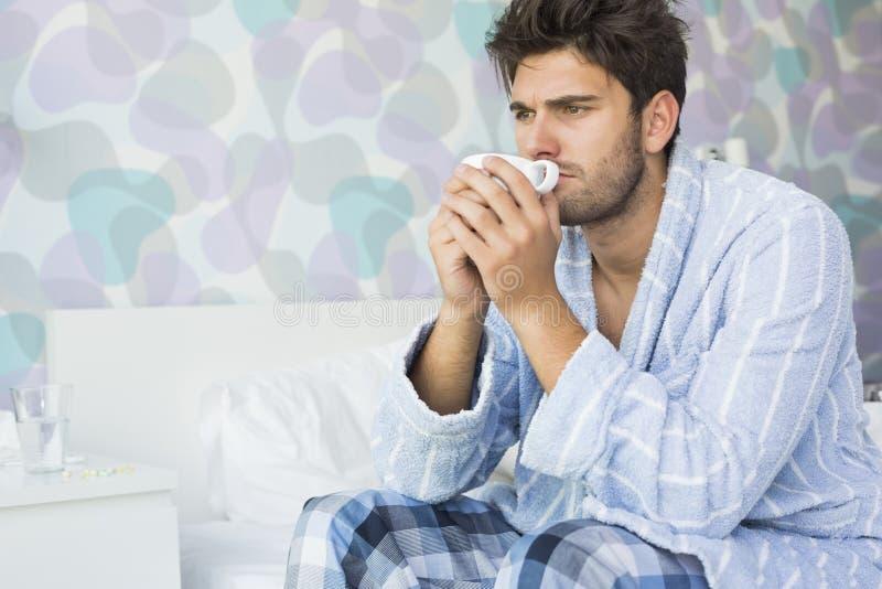 Sjuk man som dricker kaffe, medan sitta på säng hemma arkivfoto