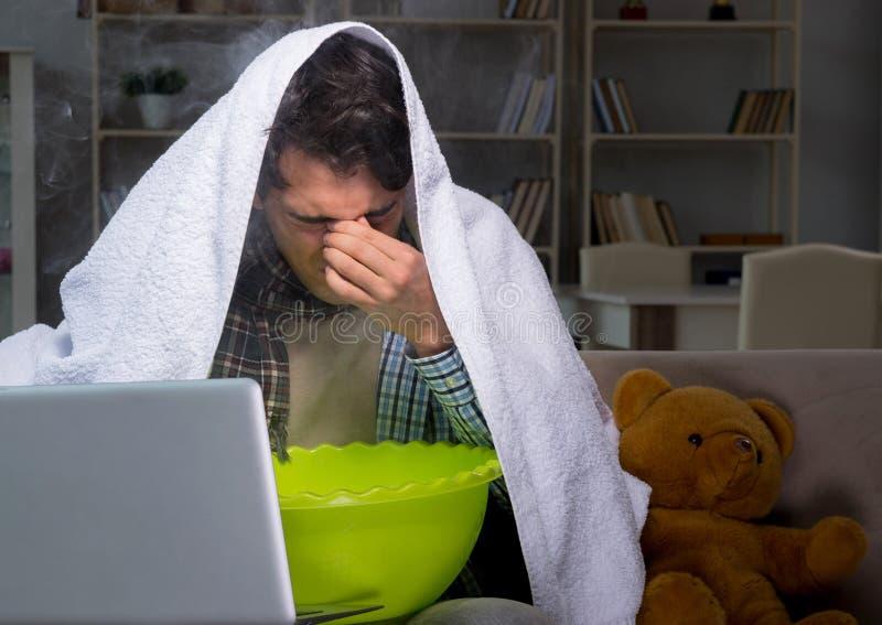 Sjuk man som g?r inandning p? natten i hem arkivbild