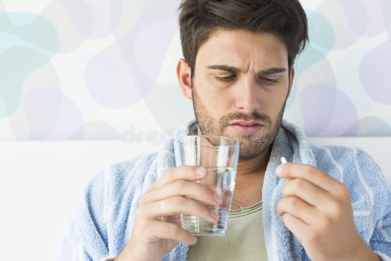 Sjuk man som hemma tar medicin i sovrum arkivfoto