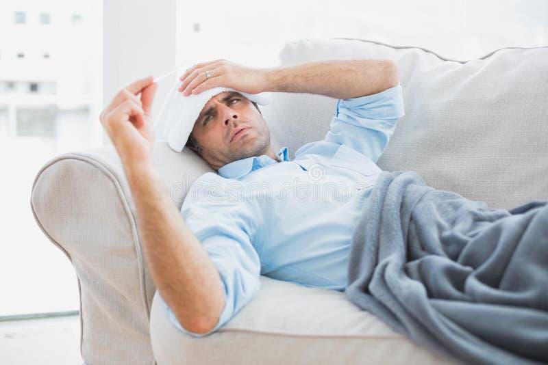 Sjuk man som ligger på soffan som kontrollerar hans temperatur under en filt royaltyfri fotografi