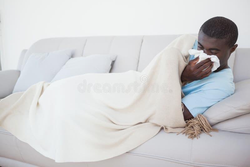 Sjuk man som ligger på soffan under en filt royaltyfri foto