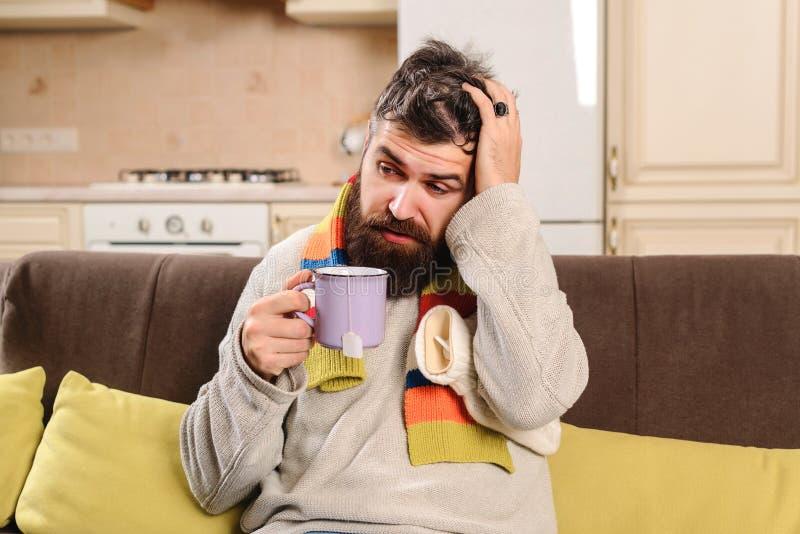 Sjuk maninnehavkopp te Ung man i tröja och halsduk Dåligt grabblidande från förkylning Utmattad sjuk man med huvudvärk sjukt fotografering för bildbyråer