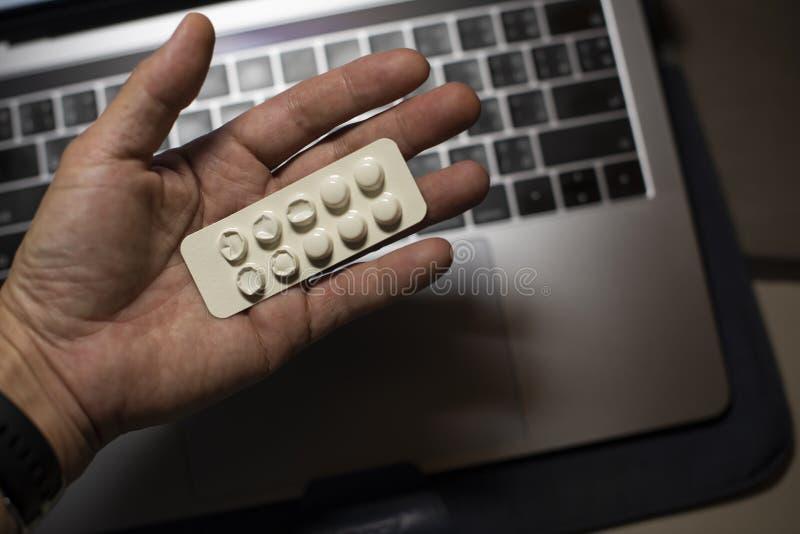 Sjuk manlig inrikesdepartementetarbetare som framme tar piller av hans funktionsdugliga utrymme, under hans funktionsdugliga stop royaltyfri bild