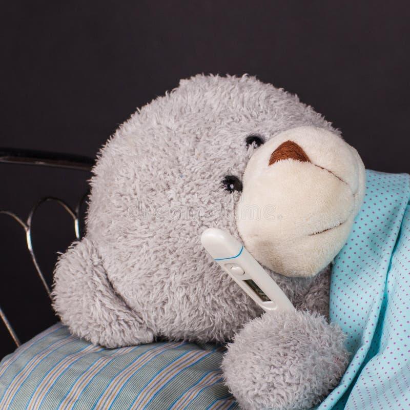 Sjuk nallebjörn som ligger i säng med en temperatur arkivbild