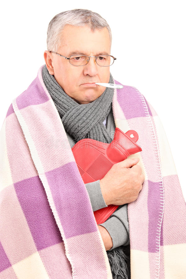 Sjuk Pensionär Med Termometern I Hans Mun Som är Dold Med Filten Arkivbild