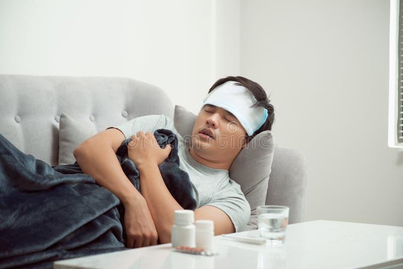 sjuk slösad man som ligger i virus för influensa för för soffalidandeförkylning och vinter arkivfoto