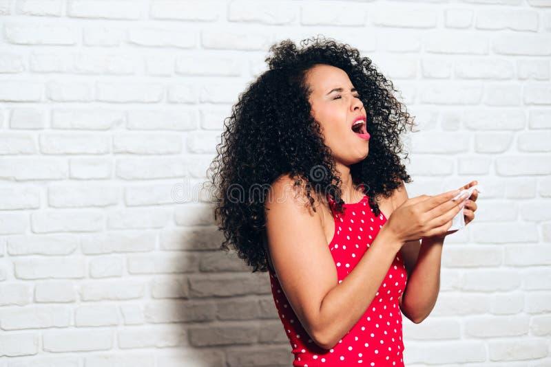 Sjuk svart kvinnaafrikansk amerikanflicka som nyser för kall allergi royaltyfri bild