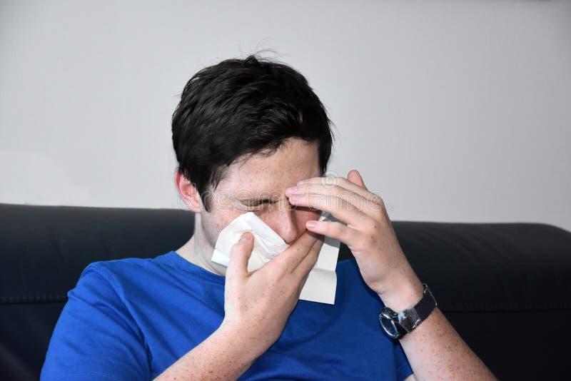 Sjuk tonårs- pojke som blåser hans näsa royaltyfri fotografi