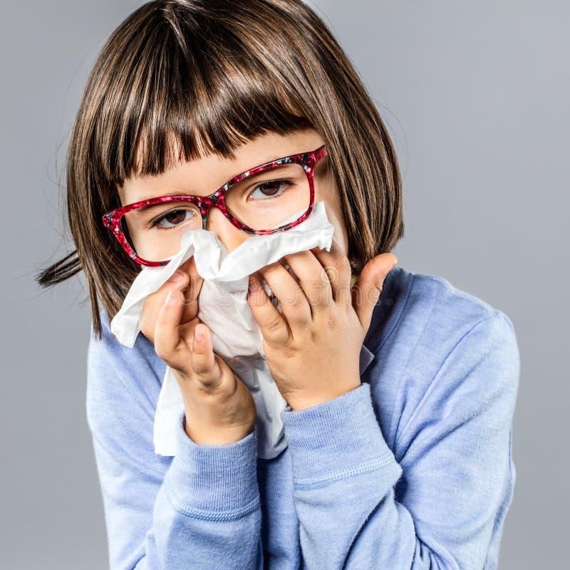 Sjuk ung flicka med glasögon som blåser näsan mot förkylning arkivfoto