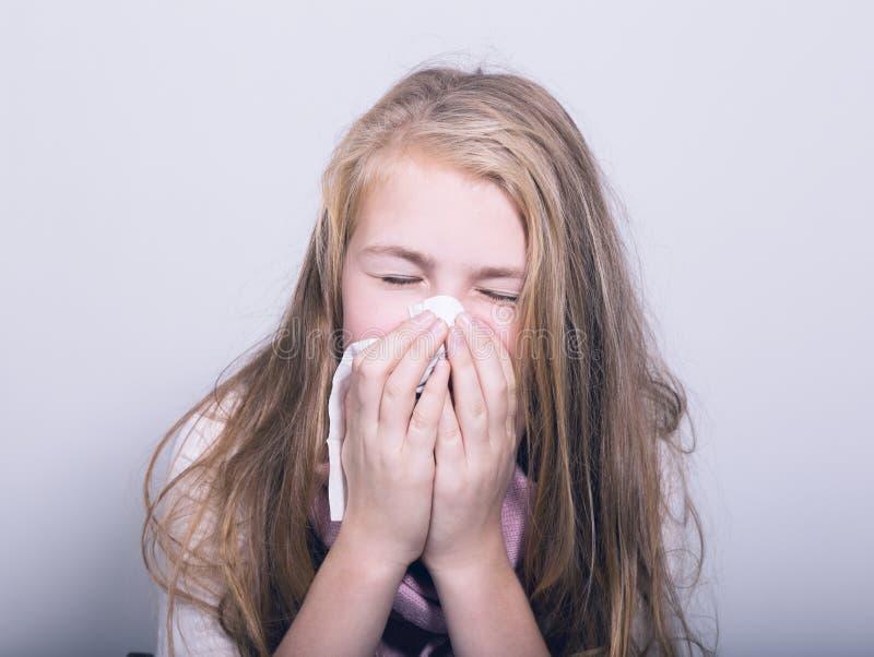Sjuk ung flicka som blåser hennes näsa med det pappers- silkespappret royaltyfria foton