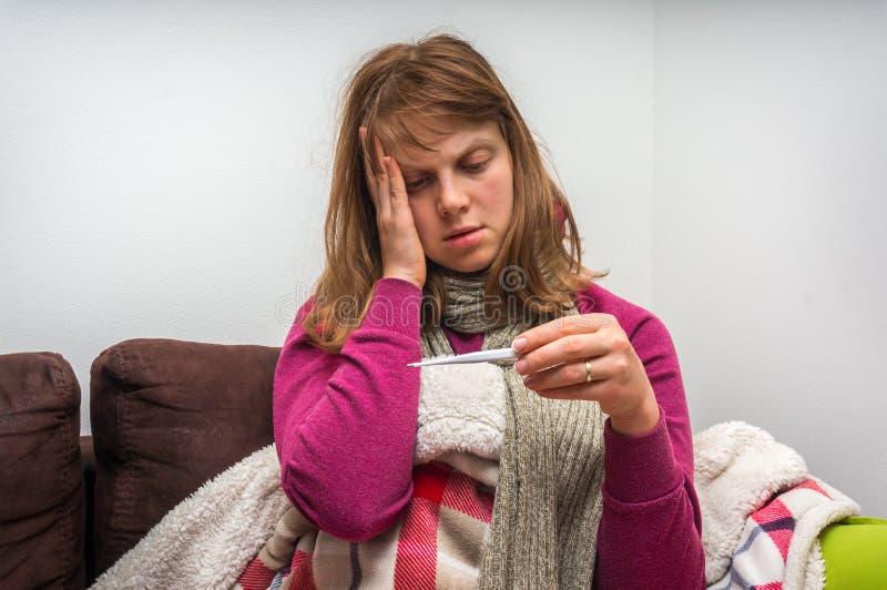 Sjuk ung kvinna med termometern som har influensa och huvudvärk royaltyfria bilder