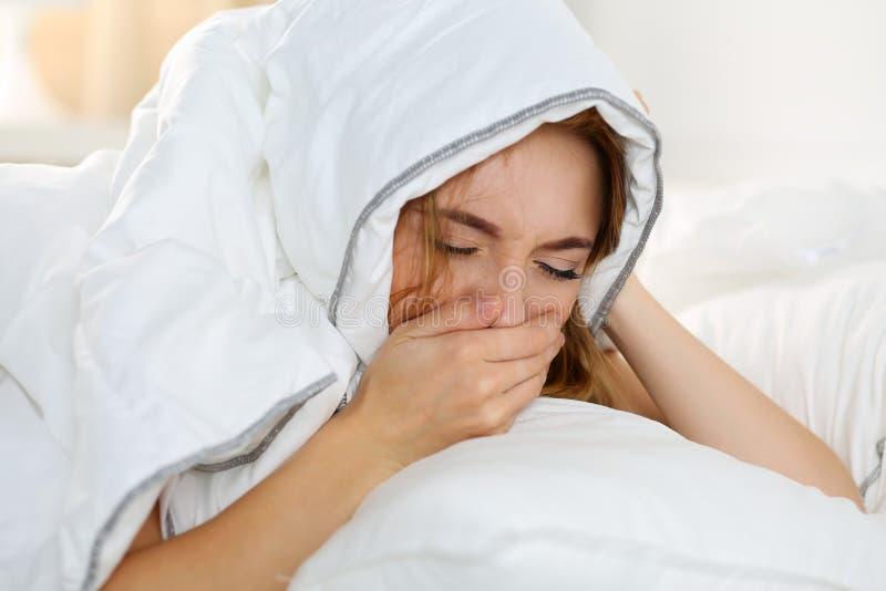 Sjuk ung kvinna som ligger i sänglidande med förkylning royaltyfri foto