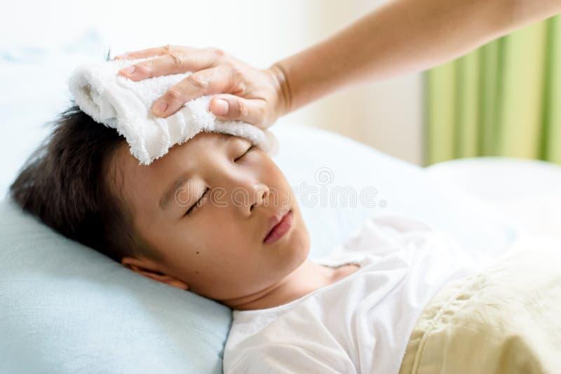 Sjuk ung pojke och sömn på sängen arkivbild