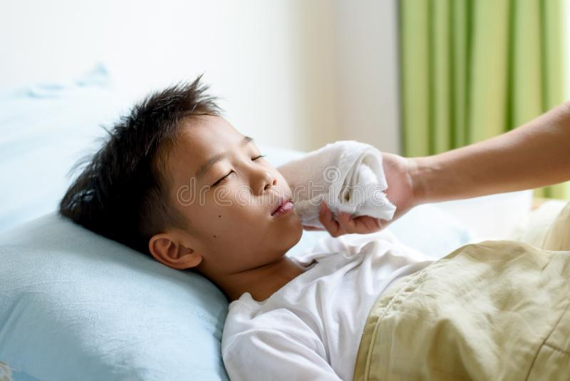 Sjuk ung pojke och sömn på sängen royaltyfri bild