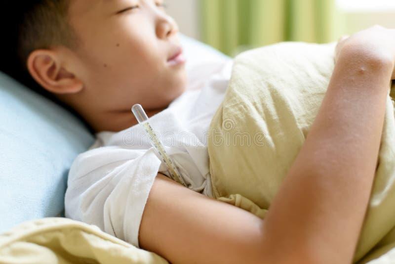 Sjuk ung pojke och sömn på sängen royaltyfria bilder