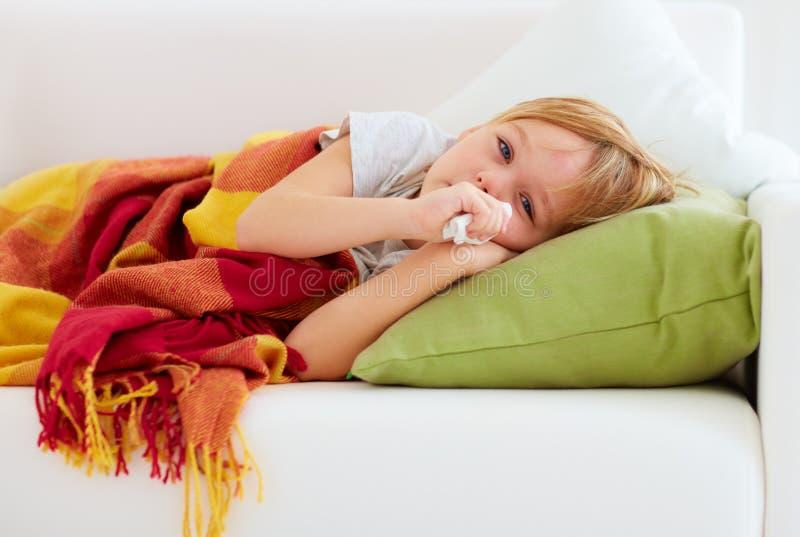 Sjuk unge med den rinnande näsan och febervärme som hemma ligger på soffan royaltyfri bild
