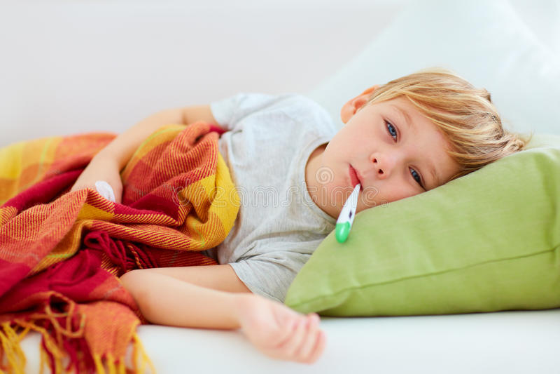 Sjuk unge med den rinnande näsan och febervärme som hemma ligger på soffan royaltyfri fotografi