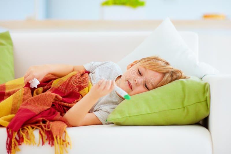 Sjuk unge med den rinnande näsan och febervärme som hemma ligger på soffan royaltyfri foto
