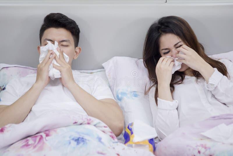 Sjuka asiatiska par som lider influensa på sängen royaltyfri foto
