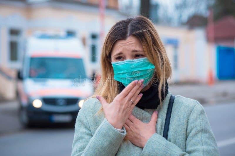 Sjuka flickor med operationsmask som känner sig sjuka när de drabbas av coronavirus royaltyfri foto