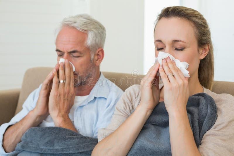 Sjuka par som blåser deras näsor som sitter på soffan arkivfoto