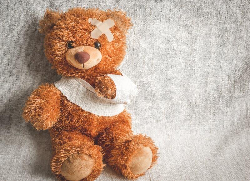 Sjukdomar för barndom för begreppsnallebjörn på textilbakgrund fotografering för bildbyråer