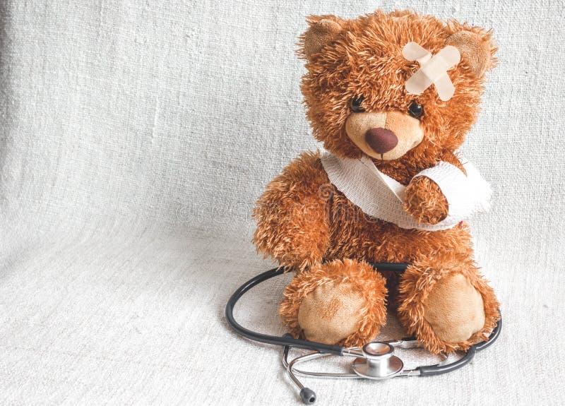 Sjukdomar för barndom för begreppsnallebjörn på textilbakgrund arkivbilder