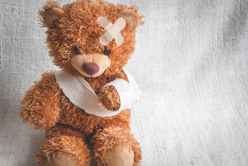 Sjukdomar för barndom för begreppsnallebjörn på textilbakgrund arkivbild