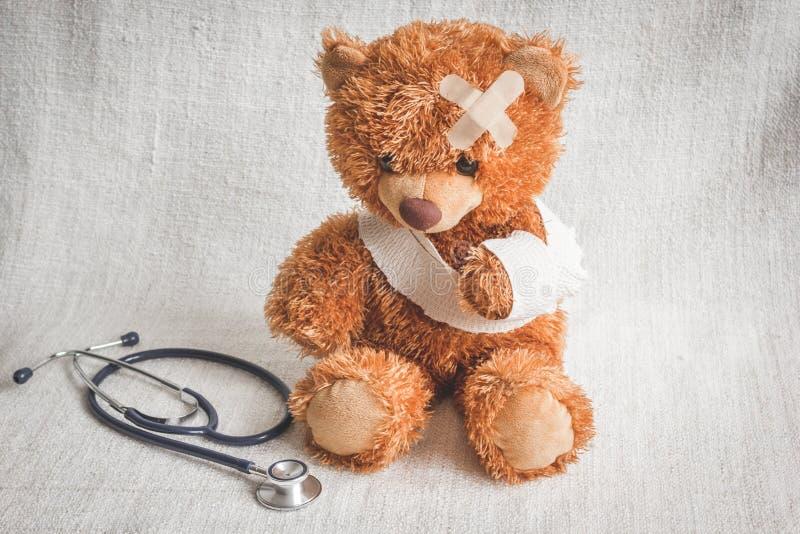Sjukdomar för barndom för begreppsnallebjörn på textilbakgrund arkivfoton