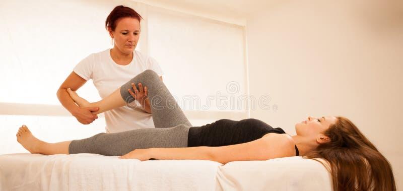 Sjukgymnastik - terapeut som övar med patienten som arbetar på le fotografering för bildbyråer