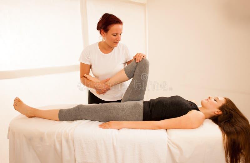 Sjukgymnastik - terapeut som övar med patienten som arbetar på le royaltyfri foto