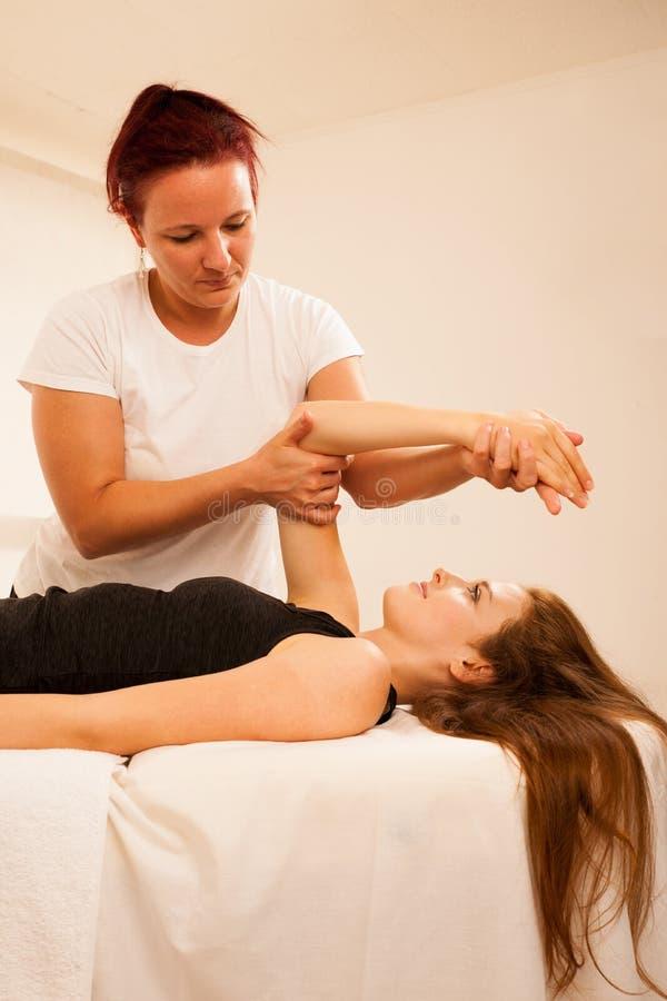 Sjukgymnastik - terapeut som ?var med patienten som arbetar p? ar royaltyfri foto