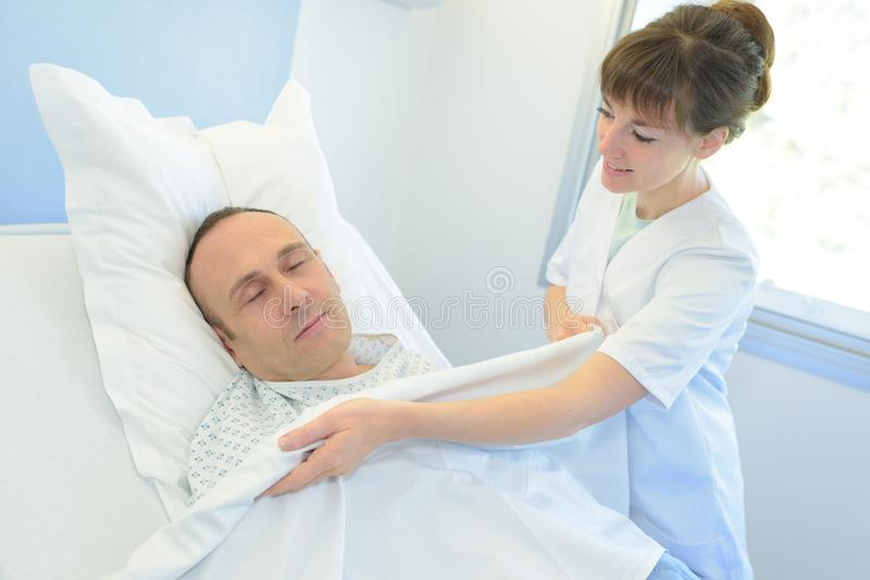 Sjukhus för säng för omsorg för sjuksköterska talande tålmodigt arkivfoton