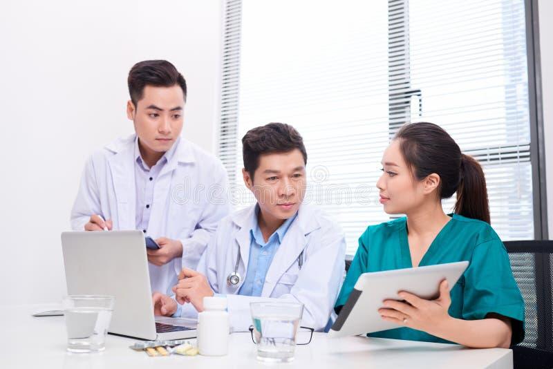 Sjukhus-, yrke-, folk- och medicinbegrepp - grupp av lyckliga doktorer med minnestavlaPCdatorer som m?ter p? det medicinska konto royaltyfri foto