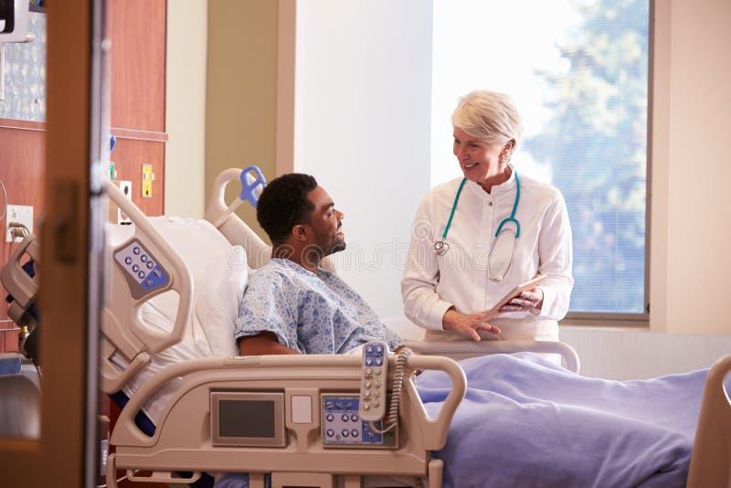 Sjukhusdoktor With Digital Tablet talar till den manliga patienten fotografering för bildbyråer