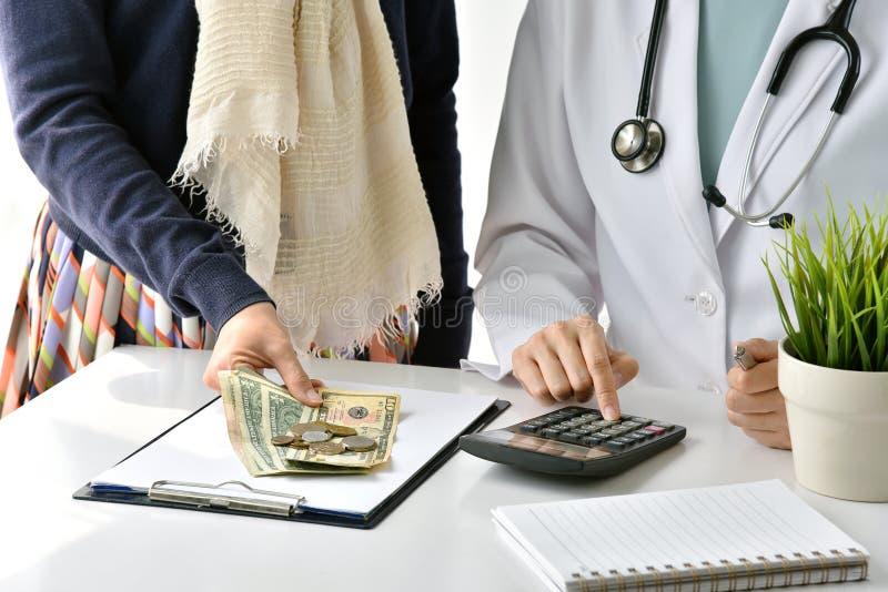 Sjukhuset och medicinsk kostnad, doktors- och kvinnapatienten beräknar på laddningar för sjukdombehandlingavgift fotografering för bildbyråer