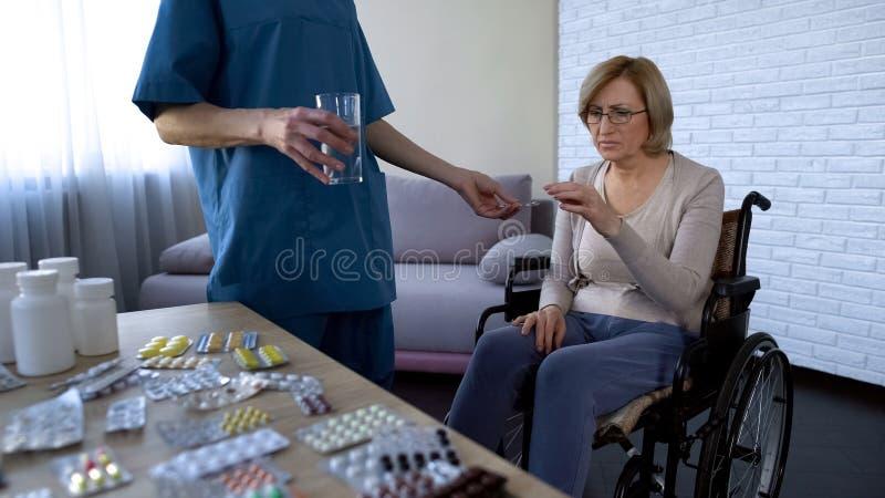 Sjukhussjuksköterska som ger preventivpillerar till den kvinnliga patienten i rullstolbehandlingrutin arkivfoto